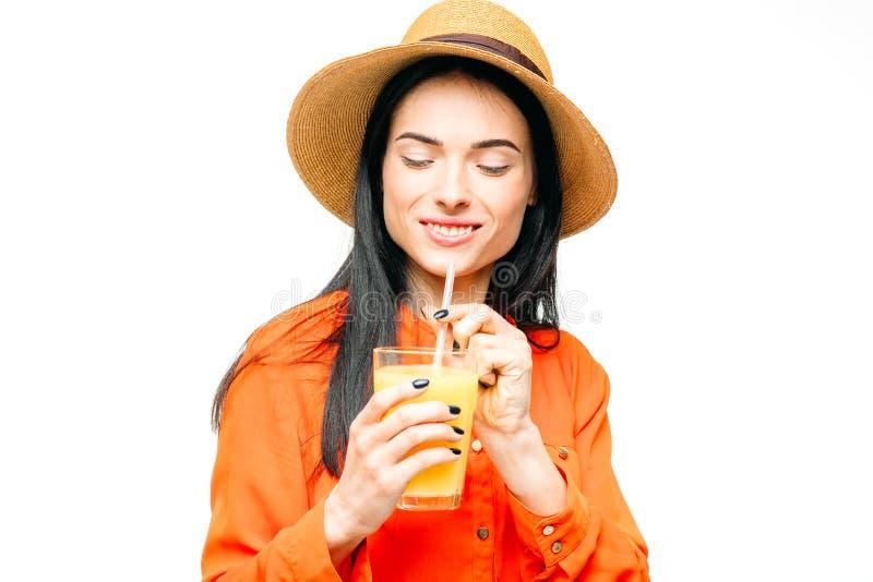 La donna beve la frutta fresca del succo, fondo bianco immagini stock libere da diritti