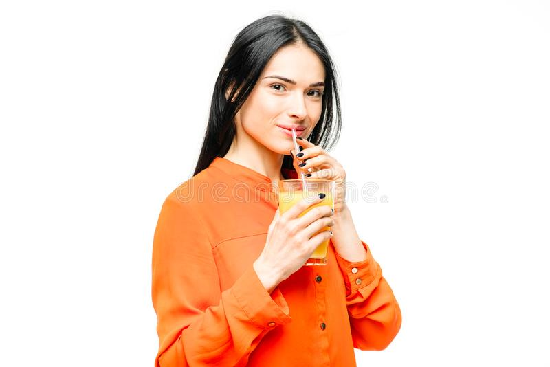 La donna beve il succo d'arancia, fondo bianco fotografia stock