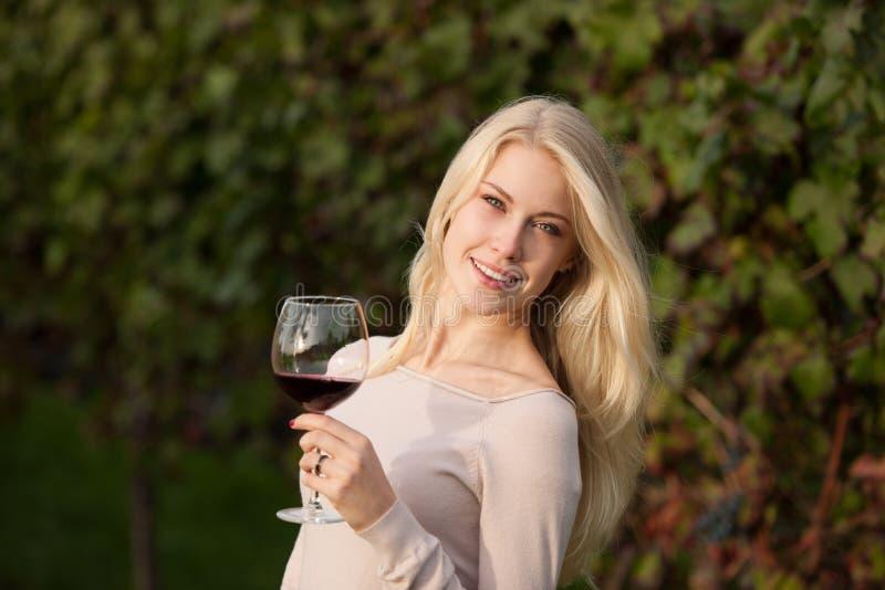 La donna beve il vino rosso in vigna fotografia stock