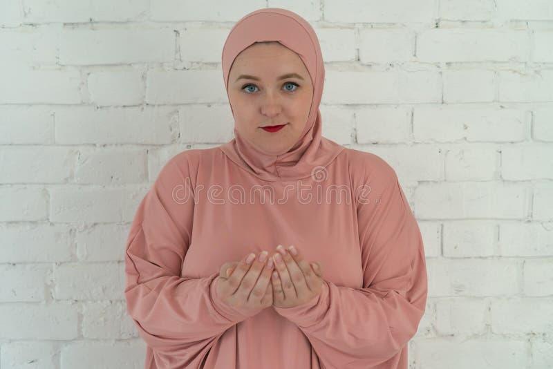 La donna bianca con gli occhi azzurri in un hijab rosa prega su un fondo bianco Concetto religioso di stile di vita della gente fotografia stock