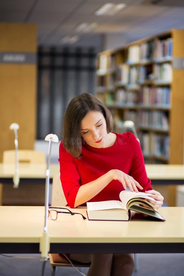 La donna in biblioteca ha trovato qualcosa molto interessante fotografie stock libere da diritti
