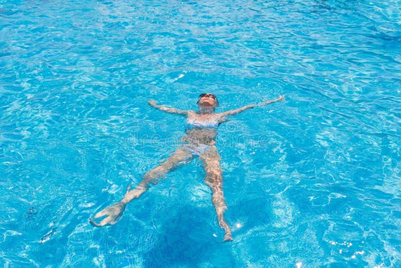 La donna in bikini che galleggia sopra appoggia nella piscina immagini stock
