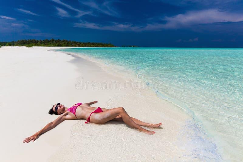 La donna in bikini porpora e rosso ha allungato sulla spiaggia immagini stock libere da diritti