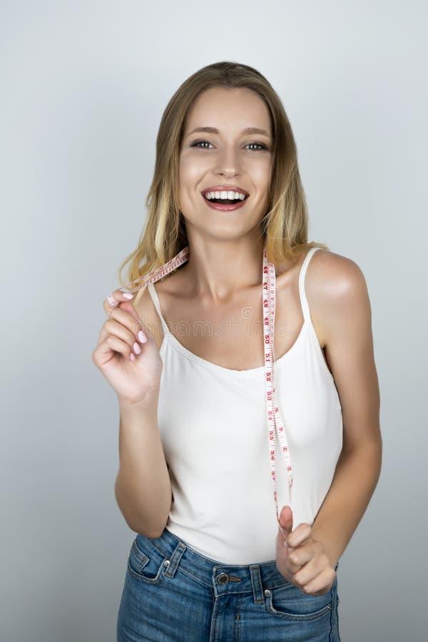 La donna bionda adatta dei giovani sembra felice tenendo il centimetro sopra il suo fondo isolato bianco del collo fotografia stock libera da diritti