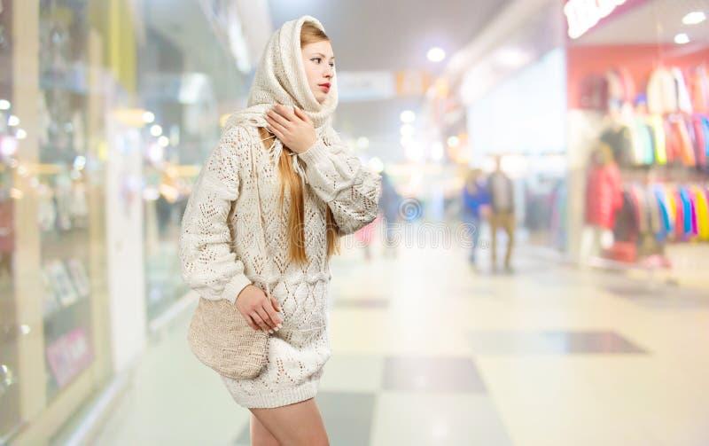 La donna bionda alla moda sorridente dei giovani nel bianco ha tricottato la sciarpa con la f immagine stock