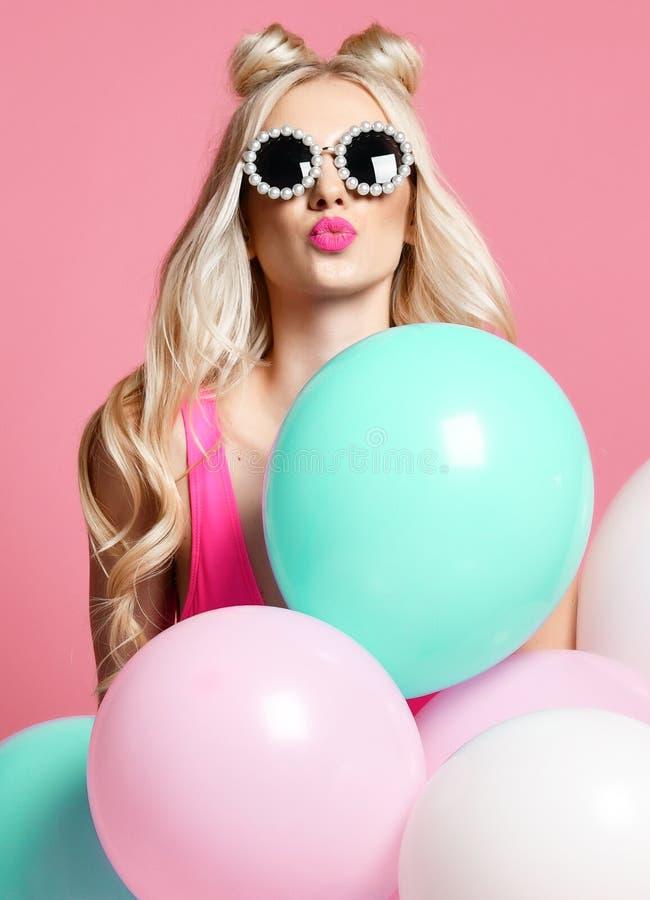 La donna bionda allegra d'avanguardia sulla festa di compleanno che si diverte con gli aerostati di colore pastello soffia il bac immagine stock
