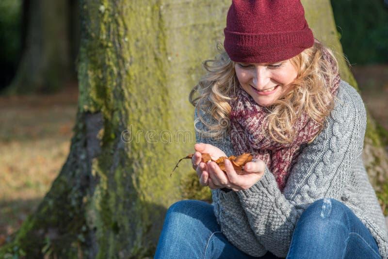 La donna bionda attraente esamina il fogliame in sua mano immagine stock