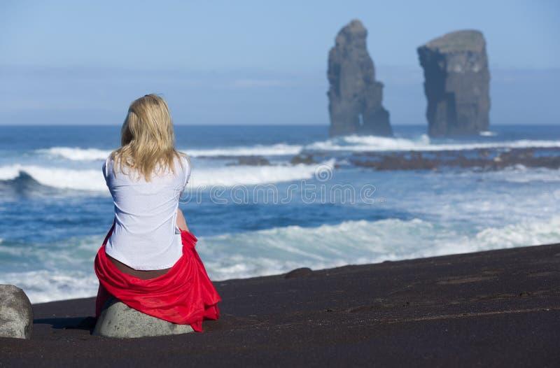 La donna bionda bella si siede sulla pietra della spiaggia, vicino alle formazioni rocciose selvagge iconiche accanto a Mosteiros immagine stock libera da diritti