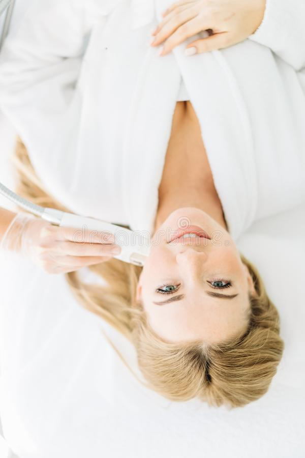 La donna bionda con capelli lunghi fa il laser del fronte che rifa la superficie al centro di bellezza fotografie stock libere da diritti