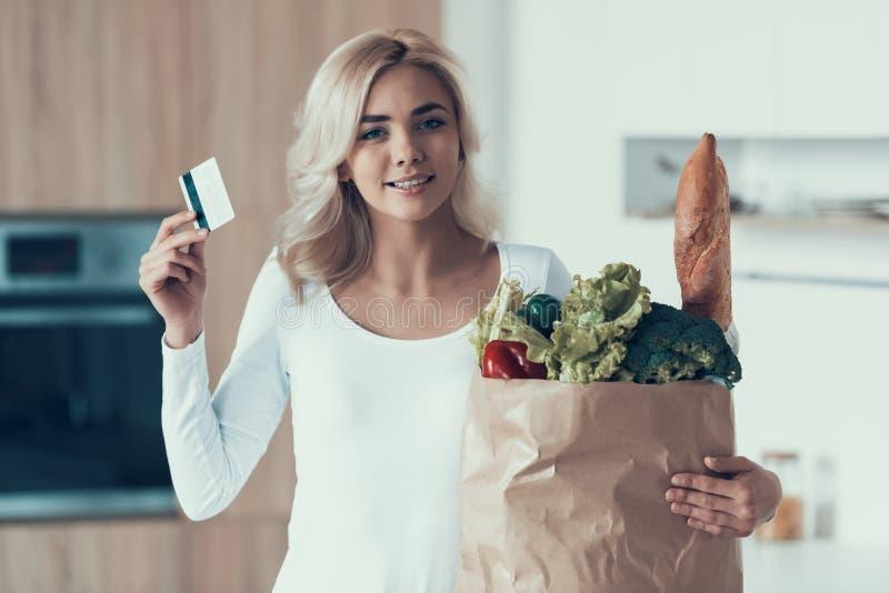 La donna bionda con la carta di credito ed il pacchetto dei prodotti sta stando nella cucina immagini stock libere da diritti