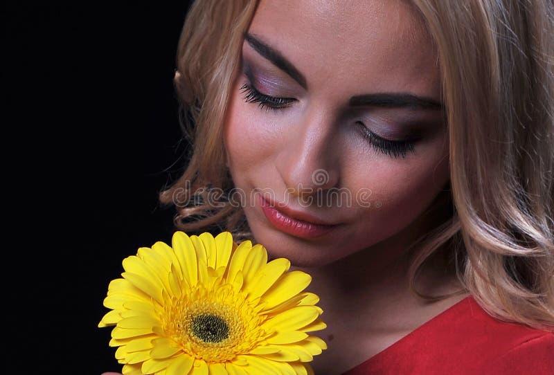 La donna bionda della ragazza su un fondo nero con un ramo del mazzo dei crisantemi gialli in mani fotografia stock libera da diritti