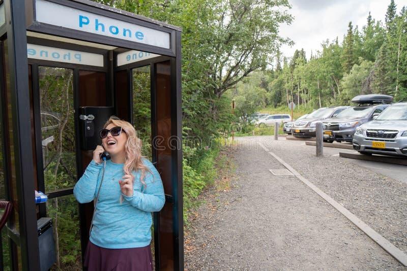 La donna bionda di risata felice parla su un telefono della cabina telefonica della linea terrestre immagine stock