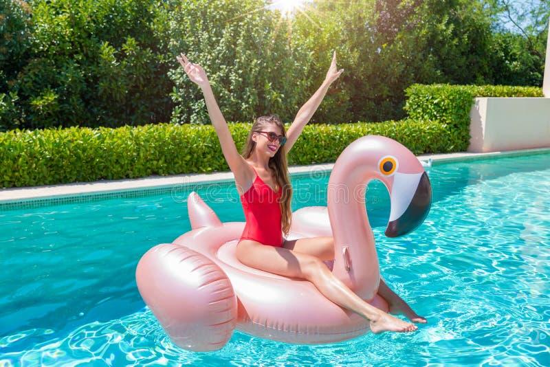 La donna bionda gode di un giorno di estate caldo nello stagno con un fenicottero galleggiabile gigante fotografie stock