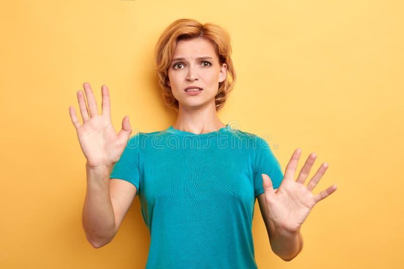 La donna bionda nervosa seria mostra le palme in camera fotografia stock