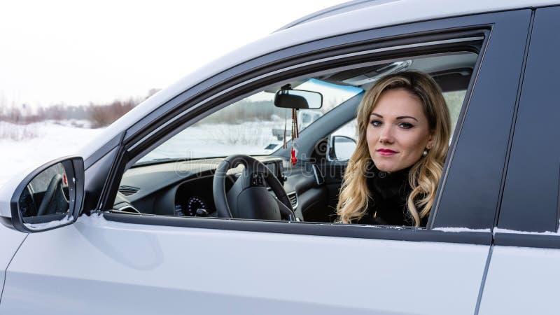 La donna bionda si siede ad un volante bianco dell'automobile ed a fissare tramite la finestra aperta immagine stock libera da diritti