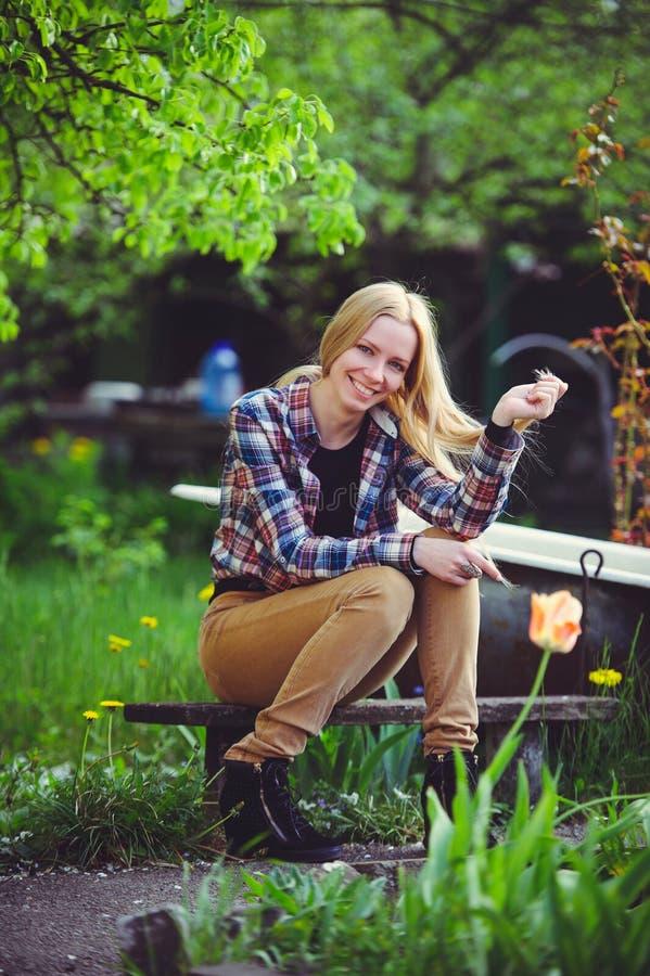 La donna bionda sveglia si siede in un giardino domestico, su un fondo dei lotti degli alberi e dei tulipani verdi, un bello ritr immagini stock