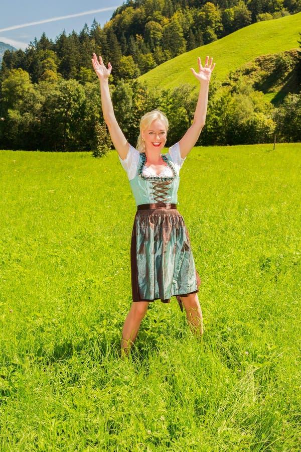 La donna bionda in un dirndl è felice in un prato verde fotografia stock libera da diritti