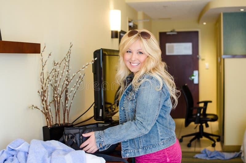 La donna bionda in una camera di albergo fa i bagagli una piccola valigia mentre prepara lasciare la casetta, concetto per la vac fotografie stock