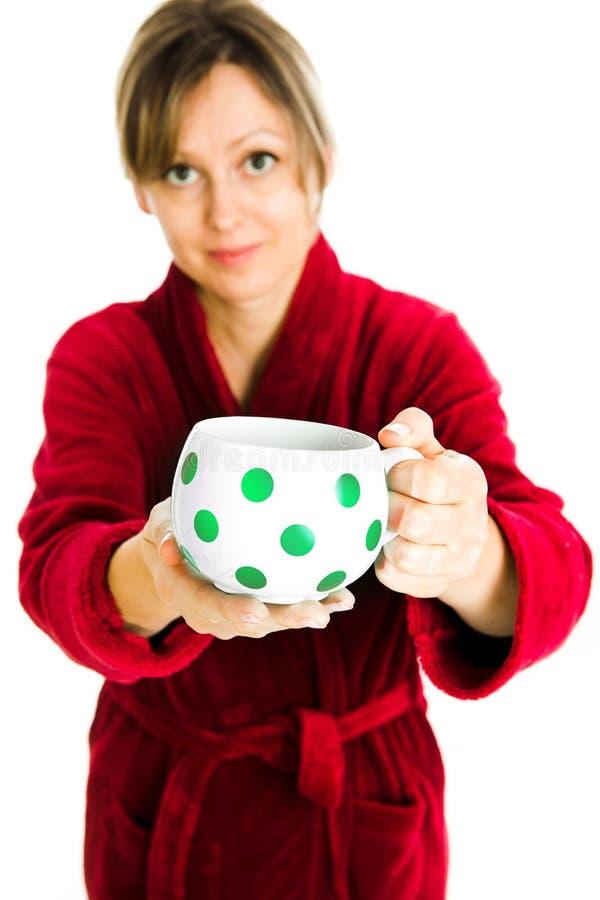 La donna bionda in vestaglia del chiaretto offre la tazza bianca con i punti rossi immagini stock