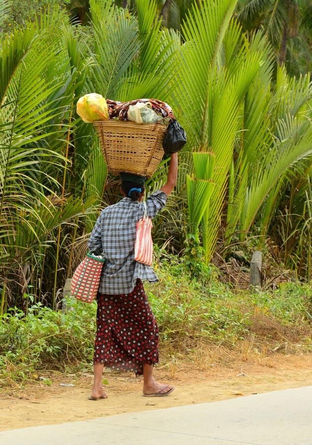 La donna birmana sta portando una borsa sulla sua testa fotografia stock