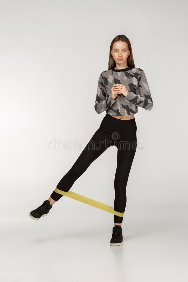 La donna in buona salute con buona costituzione fisica che fa l'allungamento risolve con le bande elastiche fotografia stock libera da diritti