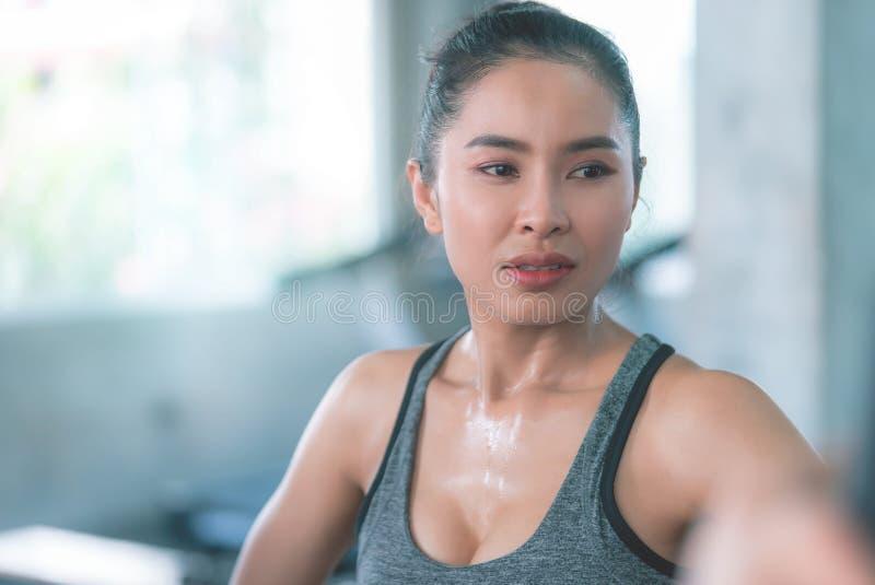 La donna in buona salute sta sudando mentre essi che si esercitano nella palestra di forma fisica fotografia stock libera da diritti