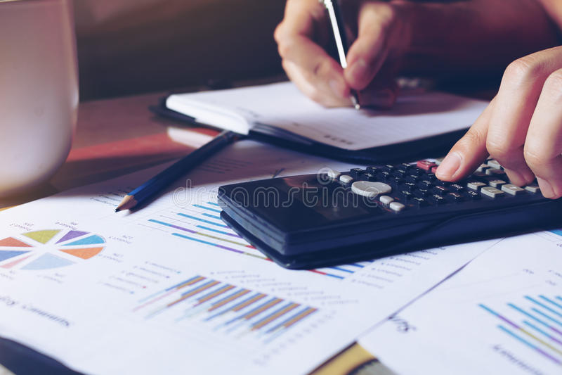 La donna calcola circa le spese e di fabbricazione sulla tavola nota a casa fotografia stock libera da diritti