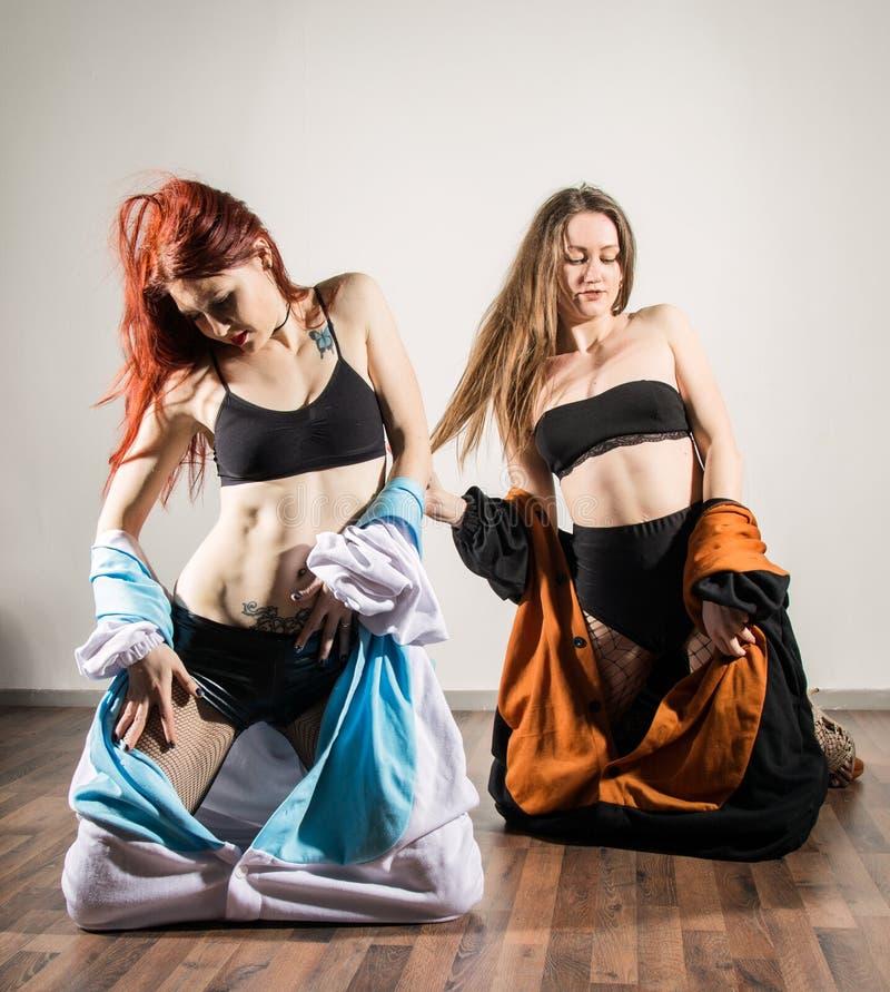 La donna calda sexy due in attrezzatura divertente si diverte nello studio fotografie stock