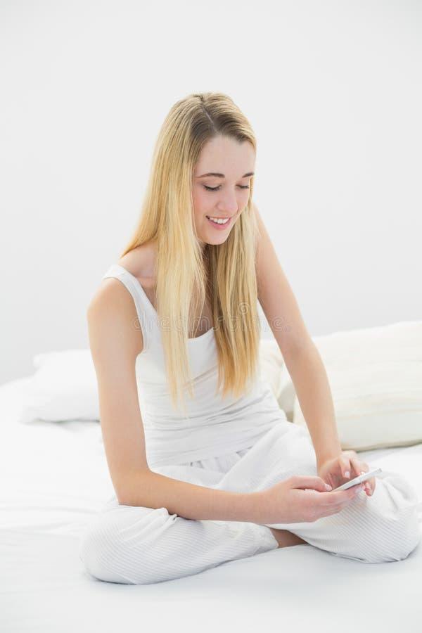 La donna calma contenta che manda un sms con il suo smartphone che si siede su lei è fotografie stock libere da diritti