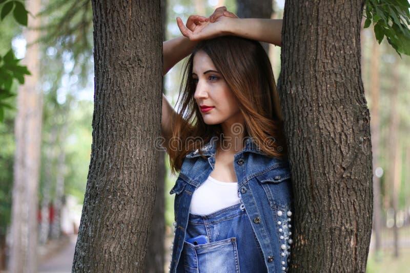 La donna in camici sta fra i tronchi di albero immagini stock libere da diritti