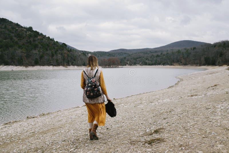 La donna cammina lungo la riva del lago immagini stock
