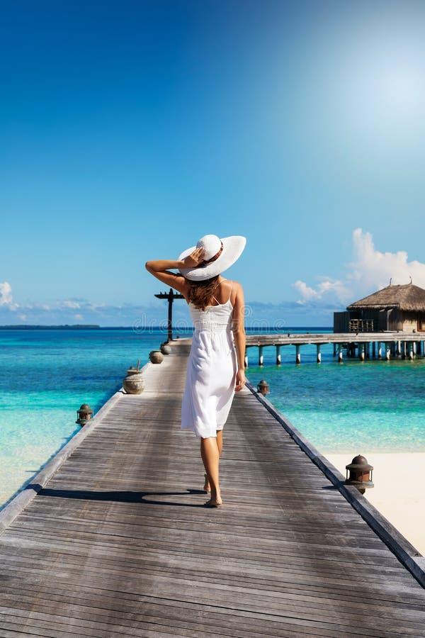 La donna cammina sopra un molo di legno in Maldive immagine stock