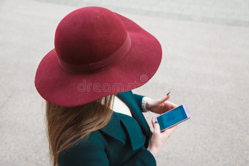 La donna in cappello passeggia intorno alla città ed utilizza il suo telefono cellulare Vista da sopra immagine stock libera da diritti