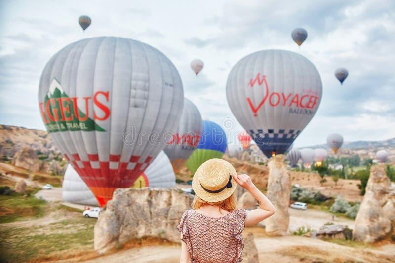 La donna in cappello sta su fondo dei palloni in Cappadocia La ragazza sta indietro sulla collina che esamina il grande numero de fotografia stock libera da diritti