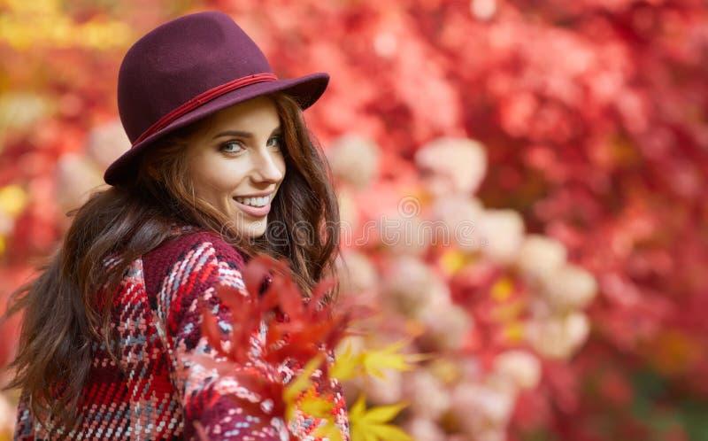 La donna in cappotto con il cappello e la sciarpa in autunno parcheggiano fotografie stock libere da diritti