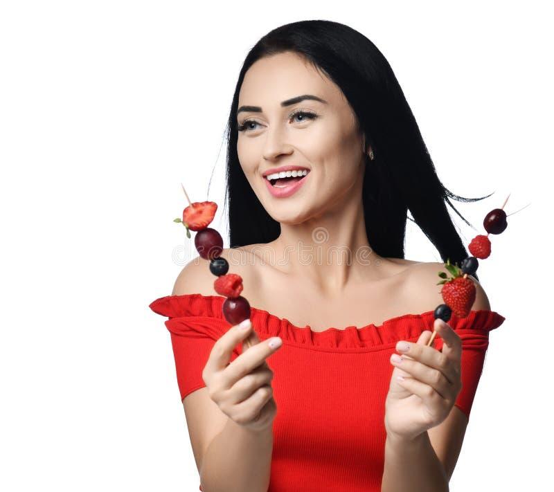 La donna castana di risata in vestito rosso alle tenute del partito porta ad elasticità due piccoli spiedi di legno con le bacche fotografie stock