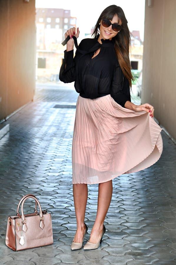 La donna castana elegante felice con gli occhiali da sole che indossano un rosa ha pieghettato la gonna, la blusa nera, gli alti  immagini stock