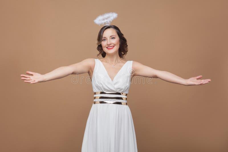 La donna castana elegante invecchiata mezzo di angelo in vestito bianco vuole a fotografie stock