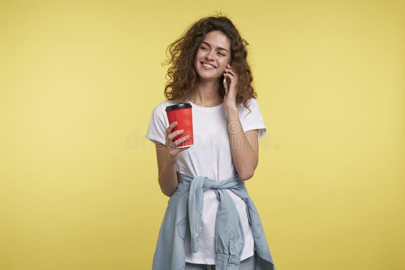 La donna castana felice con capelli ricci parla il telefono e tenendo la tazza di caffè nella mano, isolata fotografia stock libera da diritti