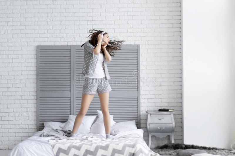La donna castana felice porta i pigiami grigi Concetto di mattina fotografie stock