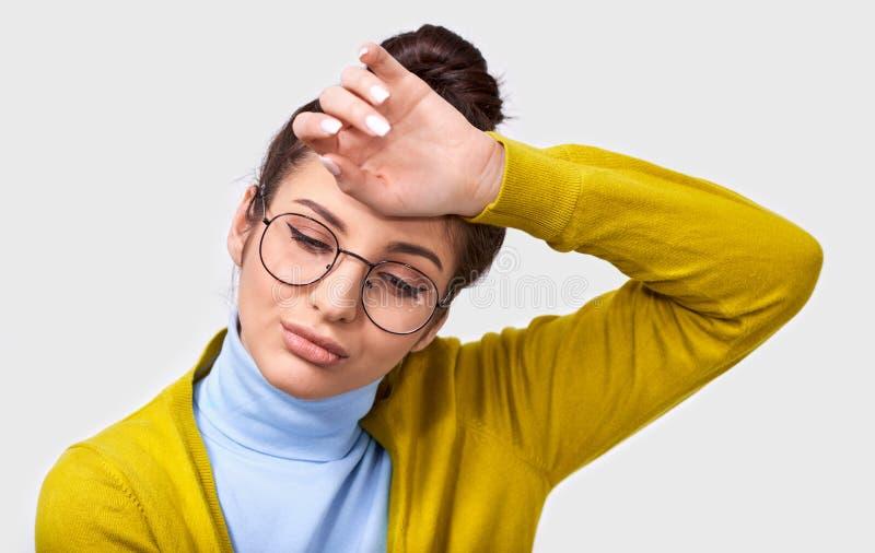 La donna castana graziosa stanca in panino ed attrezzatura casuale d'uso con gli occhiali d'avanguardia rotondi, tiene la mano su immagini stock