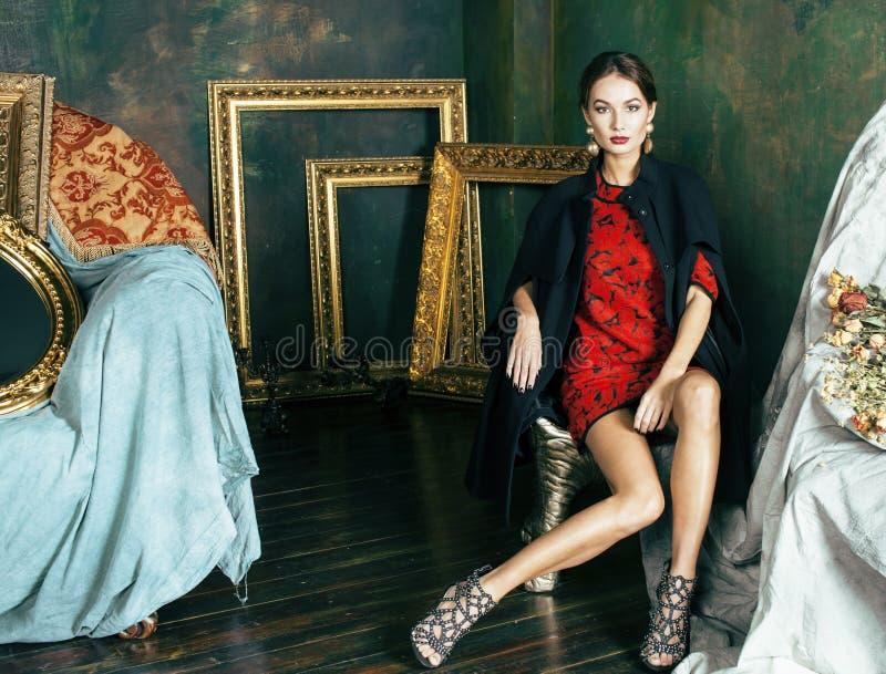 La donna castana ricca di bellezza nei telai vuoti vicini interni di lusso, modo d'uso copre, concetto della gente di stile di vi fotografie stock