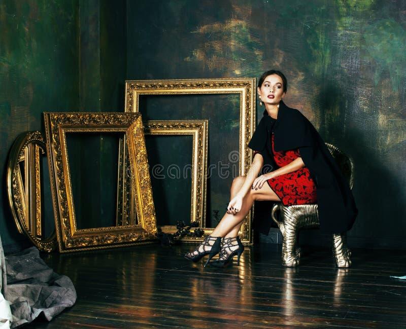 La donna castana ricca di bellezza nei telai vuoti vicini interni di lusso, modo d'uso copre, gente abbastanza reale di stile di  fotografia stock
