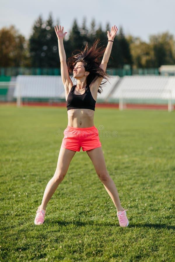 La donna castana sportiva attraente in rosa mette e allenamento facente superiore con la corda di salto nei raggi del sole allo s fotografia stock