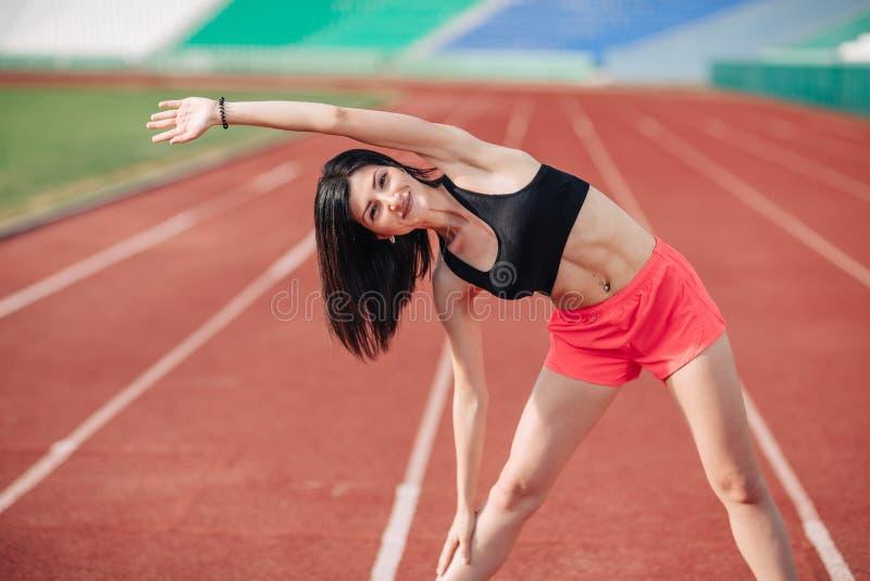 La donna castana sportiva di Attractive dell'atleta in rosa mette ed esercizio superiore che allunga allo stadio di sport nella s fotografia stock libera da diritti