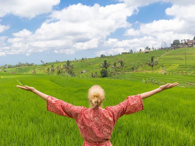 La donna caucasica alla moda rilassata che porta il kimono asiatico rosso di stile, armi rised al cielo, godente della natura pur fotografia stock libera da diritti