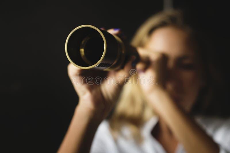 La donna caucasica sta utilizzando un telescopio fotografia stock libera da diritti