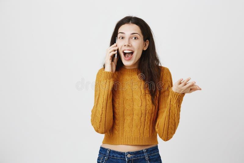 La donna caucasica stupita ed eccitata con il naso penetrante, parlante sullo smartphone e gesturing, essendo colpendo ed ascolta fotografie stock libere da diritti
