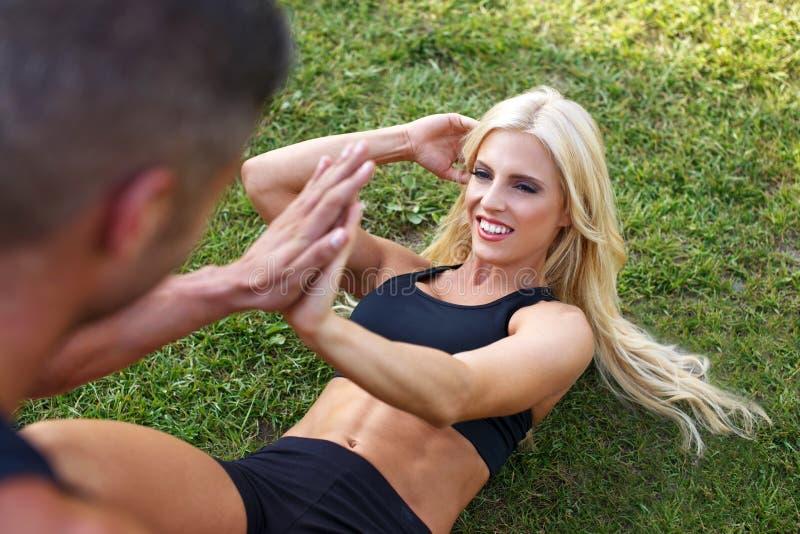 La donna che adatta della bionda fare si siede aumenta con l'uomo ciao-cinque fotografie stock libere da diritti