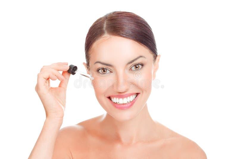 La donna che applica le anti grinze mimiche osserva sorridere dell'olio essenziale del siero del fronte fotografia stock libera da diritti